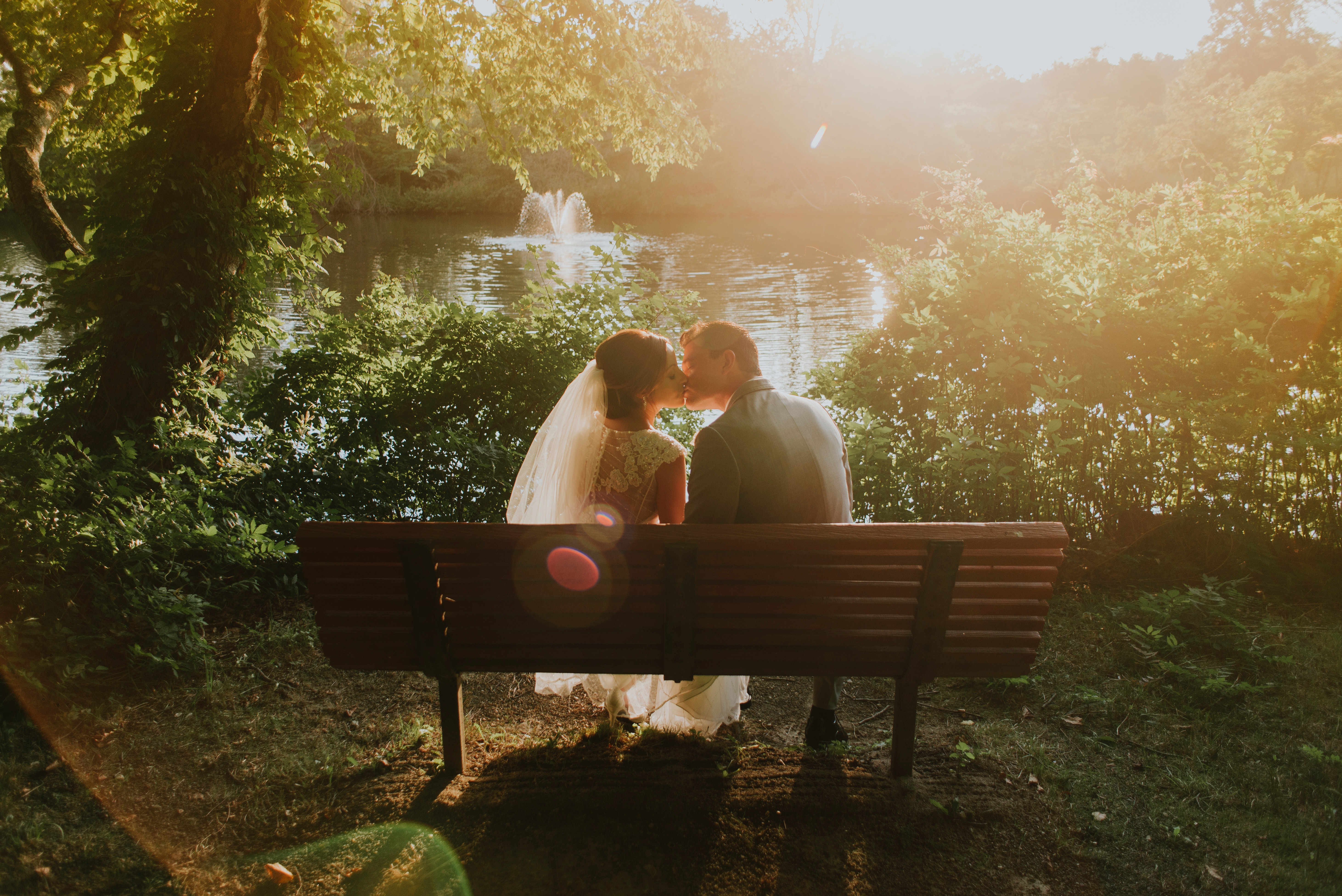 a bride and groom kissing on a bench by a pond